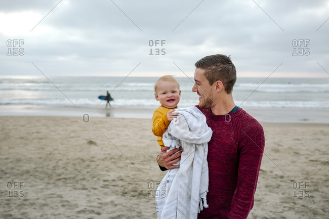 Smiling baby with blanket held by proud dad in red sweater at beach