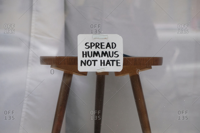 Small wooden table with sign that says spread hummus not hate