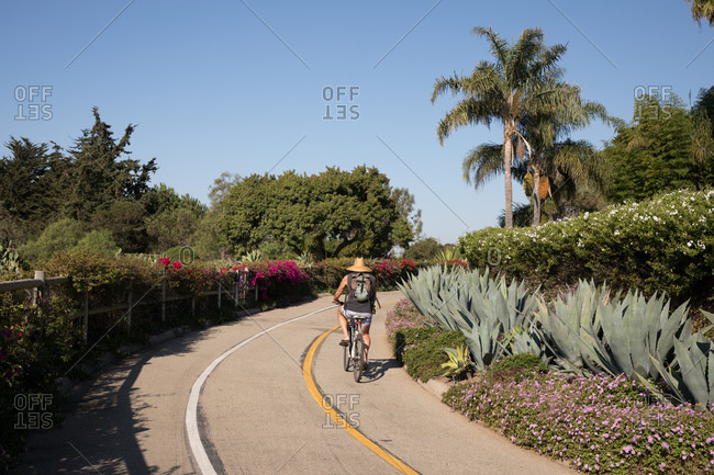 Montecito, California - October 15, 2020: Rear view of man riding bike on path near Butterfly Beach