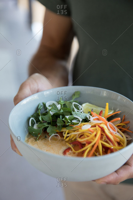 Person holding a curry dish with lime, cilantro and carrots