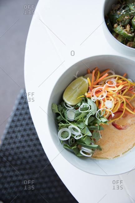 Overhead view of a curry dish with lime, cilantro and carrots