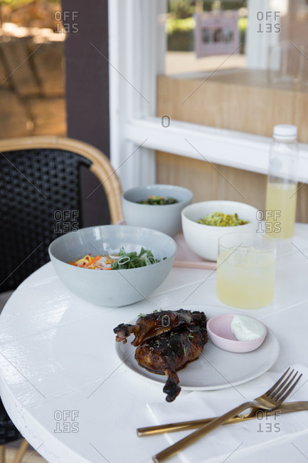 Roasted duck served with lemonade on white table