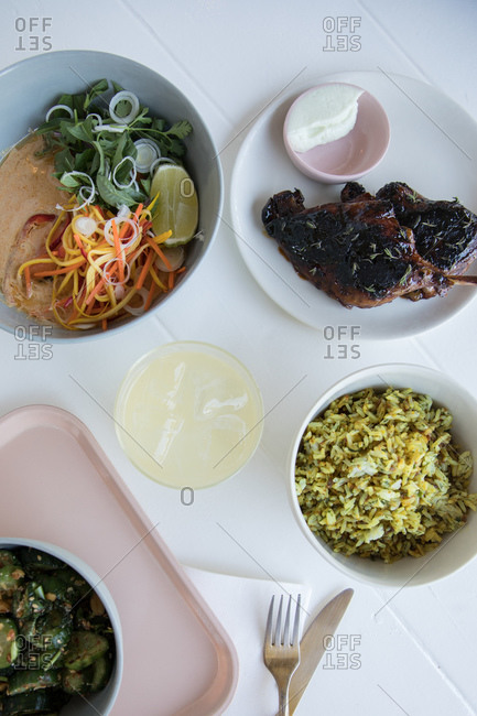 Overhead view of roasted duck served with rice and curry dish on white table