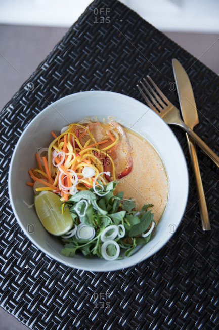 A spicy curry dish with lime, cilantro and carrots