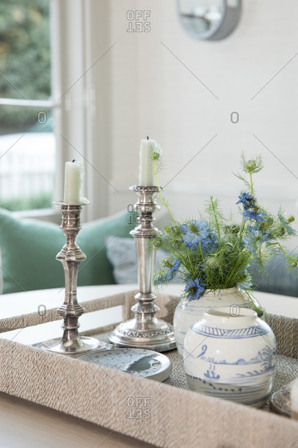 Elegant candlesticks on tray in dining room with blue flowers