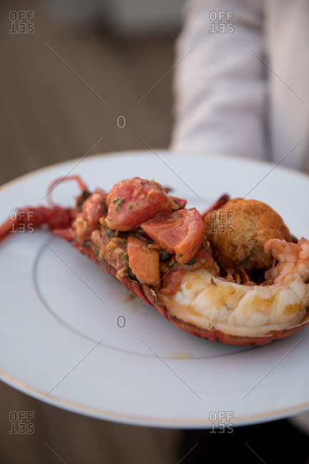 A maitre d' in a luxury hotel restaurant serving lobster