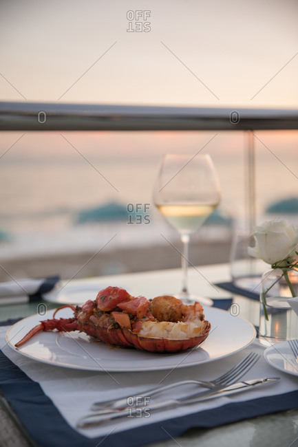 A luxury hotel restaurant with lobster on table overlooking the ocean at sunset