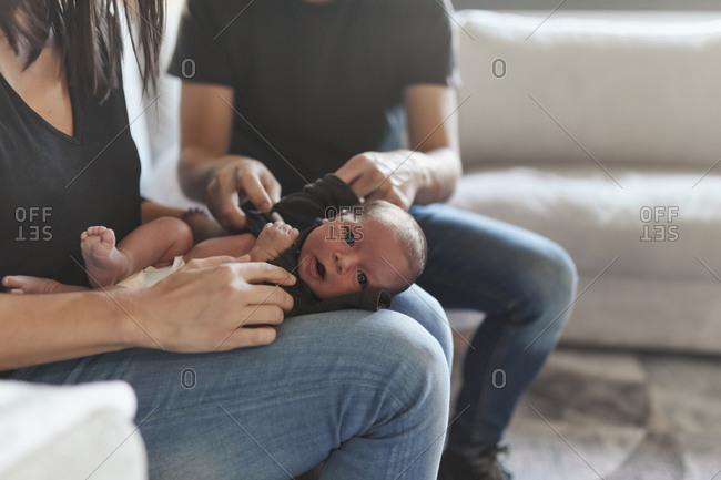 Parents sitting on sofa dressing newborn baby together