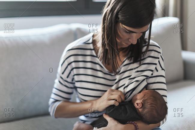 Woman sitting on sofa breastfeeding her newborn baby