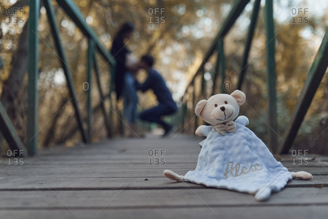 Baby's toy blanket with the name Alex on bridge with pregnant couple in background