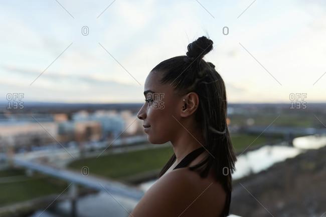 Young ethic woman standing on balcony overlooking city