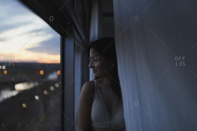Woman in bra looking out high rise apartment window at dusk