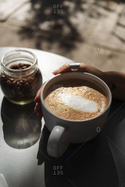 Woman hand holding a white cup with freshly brewed coffee by jar with fresh coffee grains on modern table