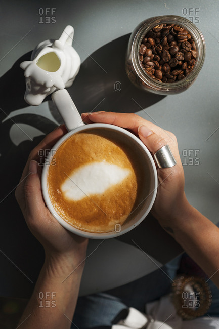 High angle view of woman hands holding a white cup with freshly brewed coffee by jar with fresh coffee grains on modern table