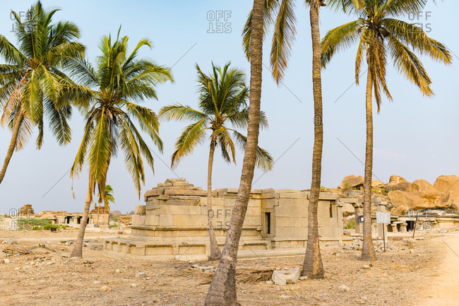 Granite temple complex in ruins surrounded by palm trees in the desert valley of Hampi, Karnataka, India