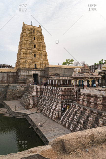 Hampi, Karnataka, India - March 26, 2019: Ancient Virupaksha Temple complex painted stairs and pond in the Hampi region