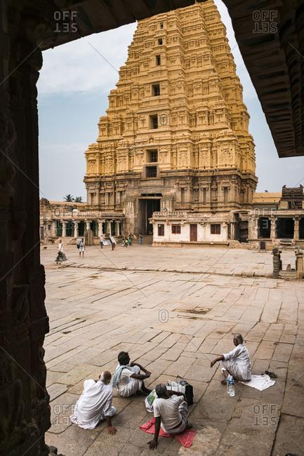 Hampi, Karnataka, India - March 26, 2019: Indian people seated in ancient Virupaksha Temple complex in the Hampi region