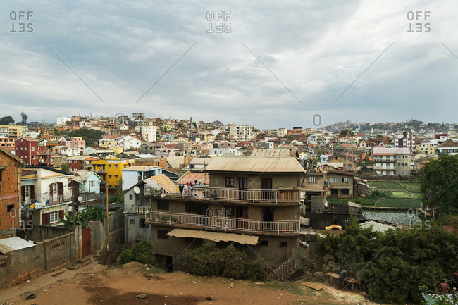 Antananarivo suburb with humble houses, colorful facades, rice fields and hills on cloudy day, Madagascar