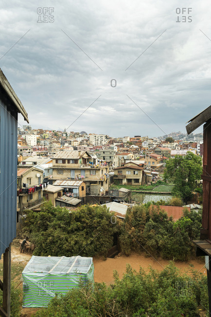 Suburb of Antananarivo with humble houses, colorful facades, rice fields and hills on cloudy day, Madagascar