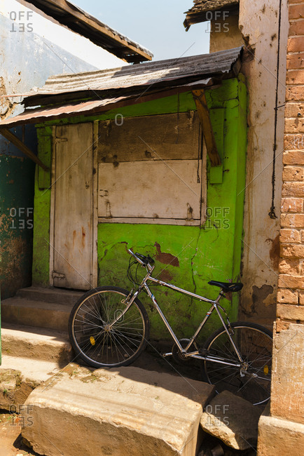 Old bike parked in front of shabby house with green facade in Fianarantsoa, Madagascar
