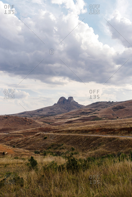 Hills and mountains on a cloudy day at sunset seen beyond dry fields in rural Fianarantsoa, Madagascar
