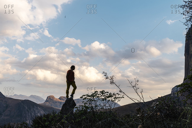 Fianarantsoa, Madagascar - October 13, 2019: Silhouette of explorer standing on rock with mountain peaks on background in Tsaranoro Valley on a cloudy day at sunset