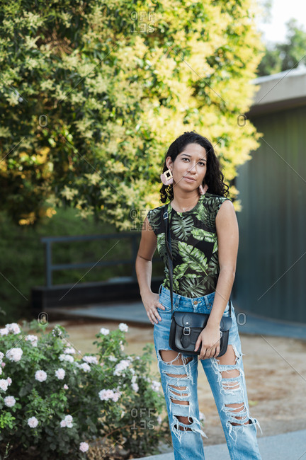 Beautiful ethnic woman in casual wear and handbag looking at camera near grey wall and colorful trees