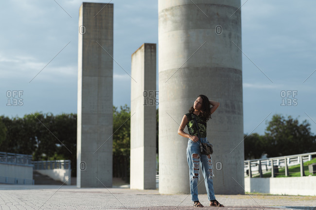 Beautiful ethnic lady in jeans and colorful t-shirt touching hair near grey concrete columns