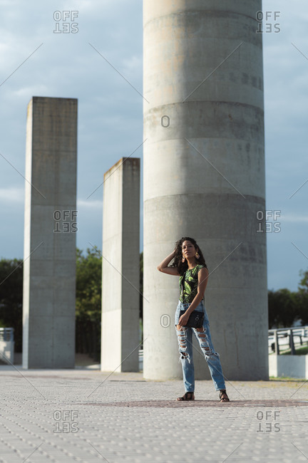 Stylish brunette Hispanic woman in jeans and colorful t-shirt touching hair near grey concrete columns