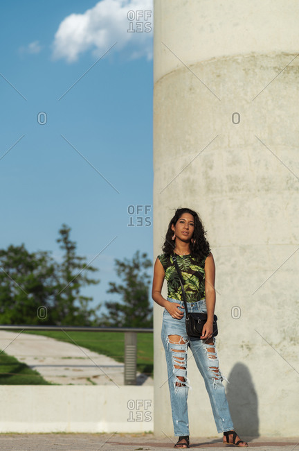 Trendy modern Hispanic woman in casual wear and jeans standing on street