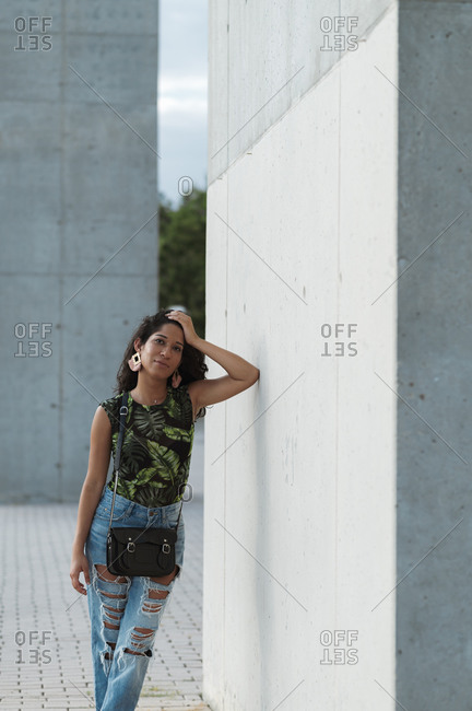 Beautiful young woman in stylish outfit leaning on concrete wall and looking at camera while touching head on street