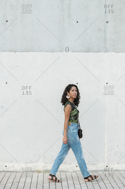 Ethnic Latina woman wearing colorful t-shirt and jeans walking in concrete urban setting