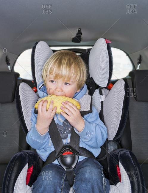 Toddler boy eating a big bread in car