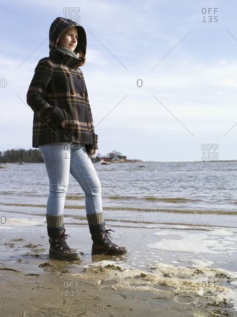 Woman standing on beach in the cold weather watching over the water