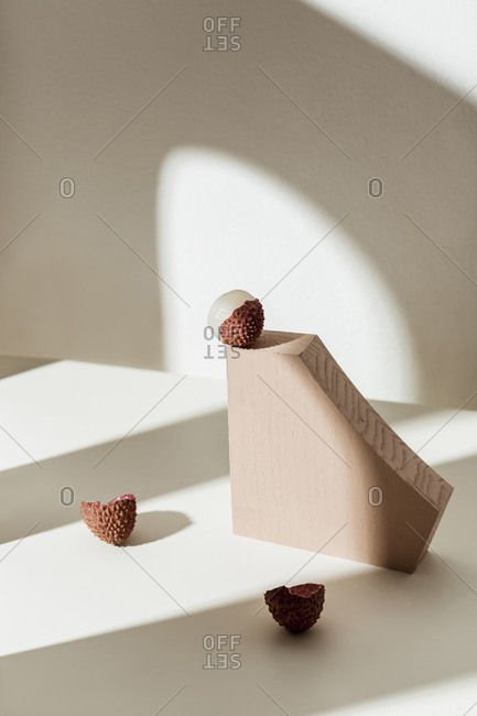 Lychee fruit on white surface with two brown blocks
