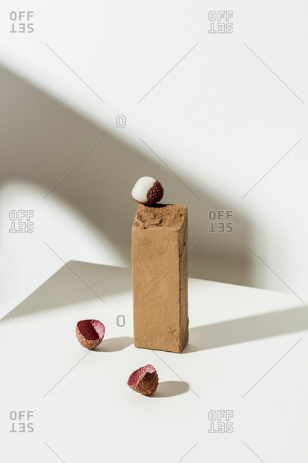 A partially peeled lychee fruit on white surface with two brown blocks