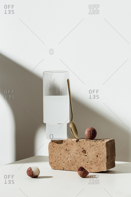 Lychee juice and fruit with peels on white surface with brown block and spoon