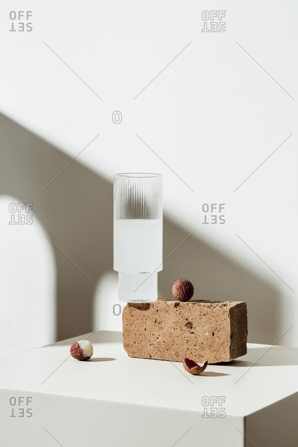 Lychee juice and fruit with peels on white surface with brown block
