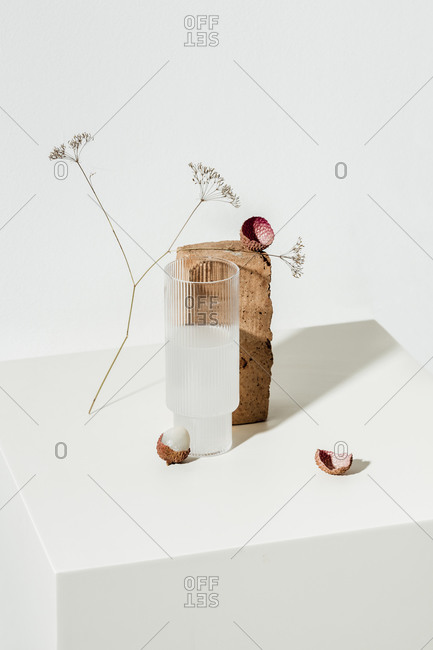 Glass of lychee juice and fruit on white surface with brown block and dried flower