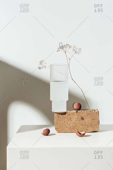 Lychee juice and fruit on white surface with brown block and dried flower