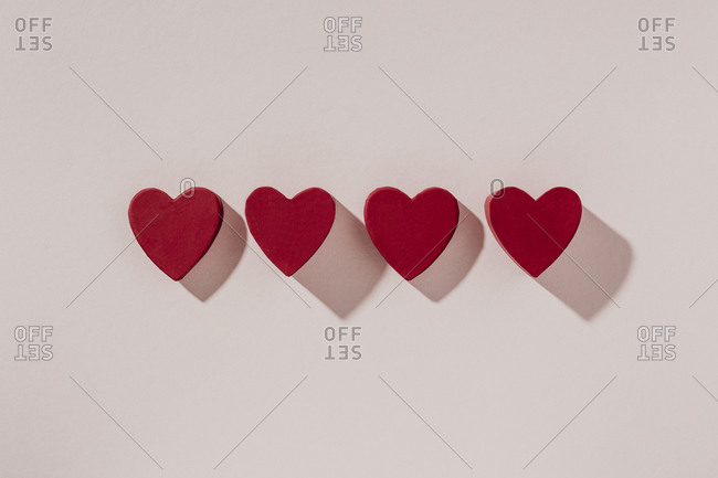 Four red hearts arranged in a row on light surface