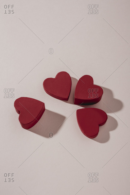 Four red hearts arranged on light surface