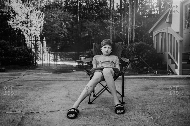 Black and white portrait of a teenage boy sitting in a driveway