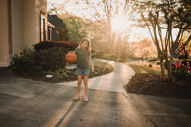 A girl bouncing a basketball outside of her home at sunset