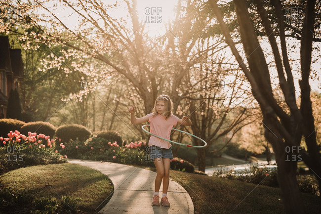 Tween girl hula hooping outside her home at sunset