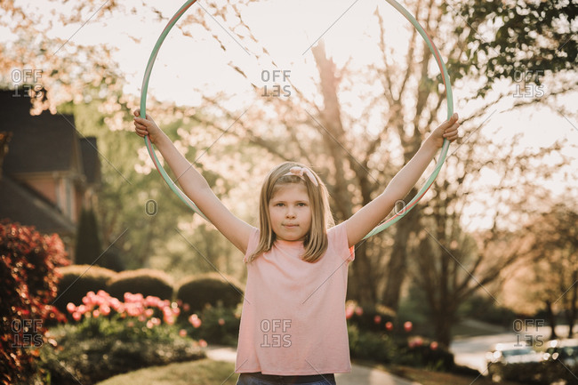 Tween girl holding a hula hooping up in the air outside her home at sunset