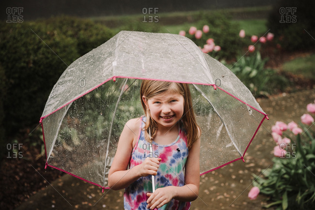 Young girl with umbrella in the rain in springtime