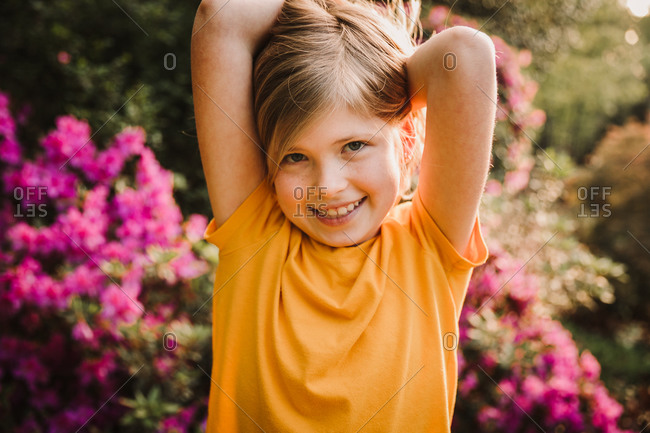 Portrait of an adorable blonde girl with her arms above her head