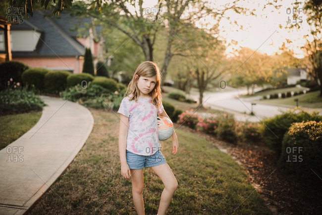 Tough girl standing with her soccer ball in her front yard at sundown