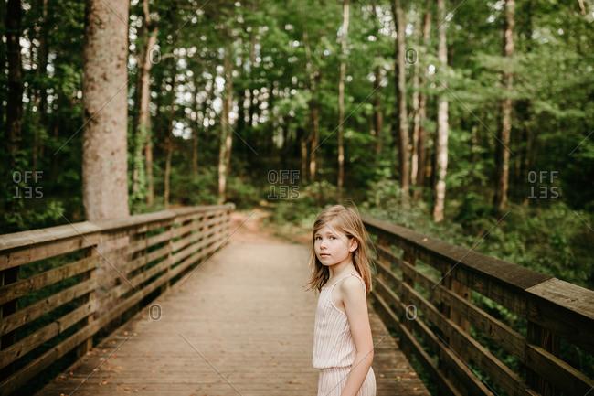 Young girl walking across a wooden bridge in the woods